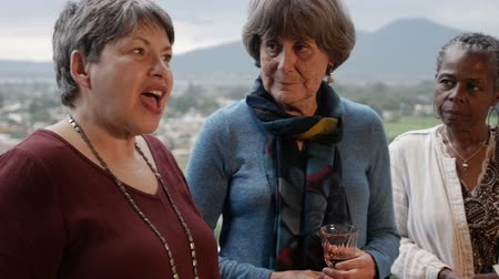 que apoia : Diverse group of attractive elderly women talking on a balcony with mountain view stabilized shot in slow motion