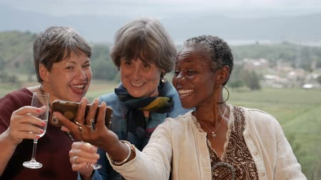 companionship : Diverse group of happy smiling multi racial senior women take a selfie with smartphone technology outside in slow motion Stock Footage