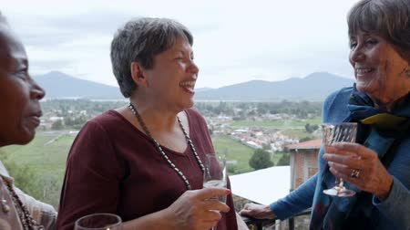 сплетни : Three diverse ethnic retired senior women in 60s laughing and sharing stories together outside with a fabulous mountain view in slow motion