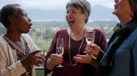 upřímný : Mixed racial group of senior women friends in their 60s laughing out loud on a balcony holding wine glasses with an amazing mountain view in slow motion