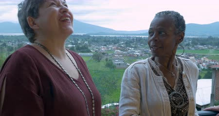 сплетни : Three mixed racial female friends over 60 talking outside overlooking a mountain view Стоковые видеозаписи