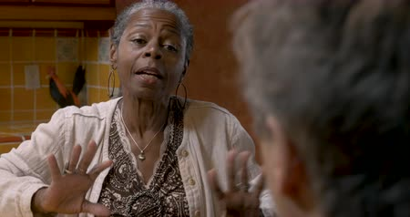 сплетни : African American woman over 50 having a serious conversation talking with her peers at a party