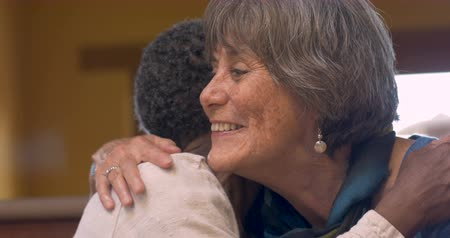 abraços : An attractive African American woman hugging a happy smiling caucasian woman both over 60