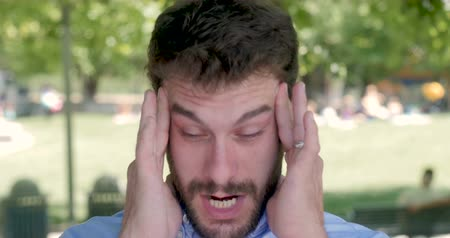aspirina : Man rubbing his temples trying to relieve himself of a headache. He could be stressed, irritated, or sick