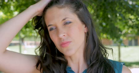 vigyorgó : Attractive woman in early 30s with shoulder length dark hair brushing it back with her hand