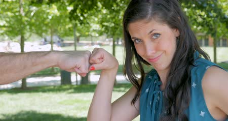 espetacular : Attractive smiling happy woman getting exploding fist bump in a park during day from a stranger Stock Footage