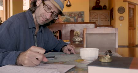 ödev : Attractive man planning his vacation using a map and notebook - dolly shot