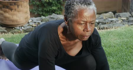 strong granny : Active senior African American woman in 60s doing low lunge yoga pose Stock Footage