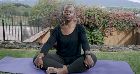 ruhanilik : Retired African American woman in her 60s resting quietly on a yoga mat meditating - dolly shot
