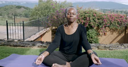 strong granny : African American elderly woman in her 60s sitting quietly mediating with her legs crossed on a yoga mat outside - medium dolly shot