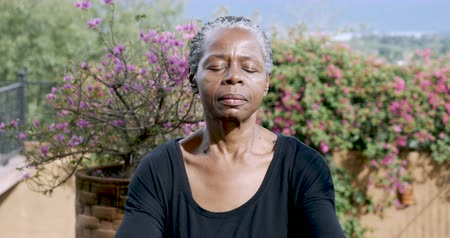 respiração : Attractive African American senior woman meditating outdoors with her eyes closed focusing on her breath - dolly shot Vídeos
