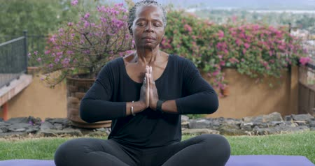 ruhanilik : Senior African American woman in her 60s finishing her yoga routine with a namaste - push out