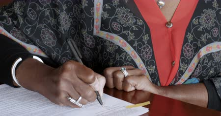 подпись : Black senior woman over 50 signing her name on legal paperwork or contracts with her signature