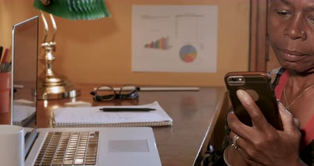 adresář : Tilt up of mature black woman working and making a phone call on smart phone at her desk with a laptop computer Dostupné videozáznamy