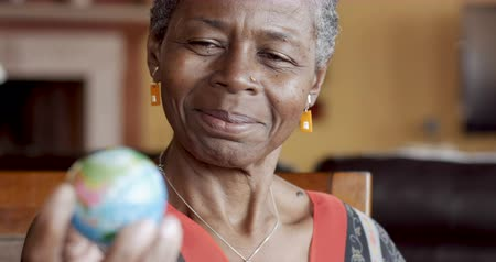 mapa : Happy smiling African American mature woman over 50 looking a world globe for places to travel