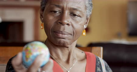 mapa : Rack focus of attractive African American senior woman over 50 looking at small world map globe in her hand Wideo