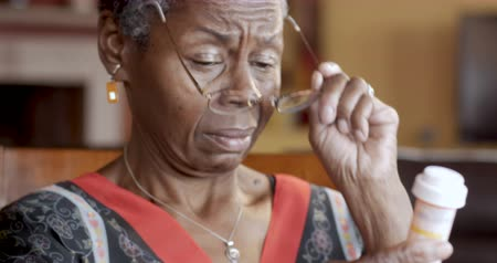 straining : Black senior woman putting on glasses to read medication instructions of her prescription bottle for her health care