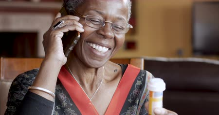 africký : Happy smiling black woman over 50 talking and completing her prescription drug order on her cell phone with her pharmacy Dostupné videozáznamy