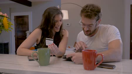 touchpad : Attractive millennial couple in their early 30s online shopping together in their home on a digital tablet and a credit card - crane shot Stock Footage