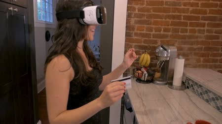 fejhallgató : Push in of an attractive woman making her digital selections in a virtual store shopping with a credit card and a VR headset in slow motion