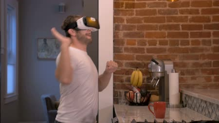 participante : Attractive man in early thirties or late twenties using VR headset giving virtual round of high fives to an imaginary crowd in his home in slow motion Vídeos