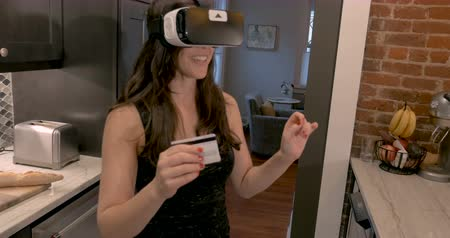 выбирать : Beautiful woman in early 30s selecting items in a virtual reality store wearing VR in her galley kitchen in the morning