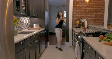 dancer : Happy, smiling attractive woman in her early 30s enters her galley kitchen dancing with her smart phone while checking her notifications and messages Stock Footage