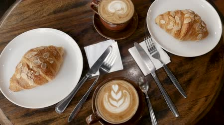 gastronomia : Overhead of gourmet breakfast with fancy coffee drinks such as a cappuccino or latte coffee With heart shape and almond croissants on a wooden table