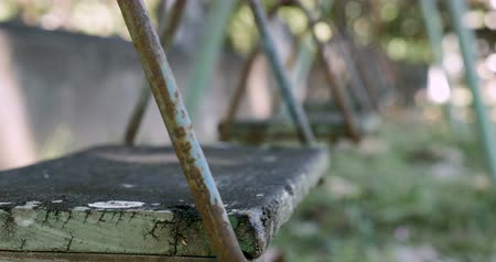 apodrecendo : Close up of an old wooden swing deteriorating from age and the weather in an abandoned playground
