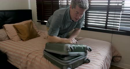 preparado : Tourist man having trouble fitting all his belongings in his suitcase so he cant close his luggage