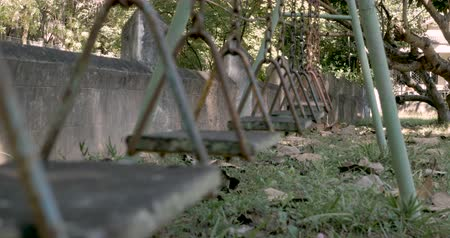 apodrecendo : Handheld low angle of a swing moving back and forth in abandoned playground