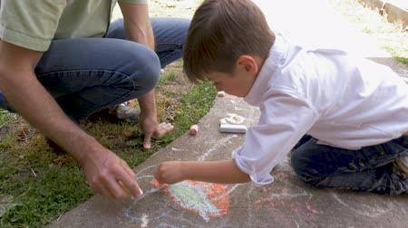 companionship : Father and son drawing on a sidewalk outside with chalk on a warm spring or summer day handheld in slow motion