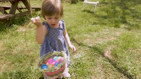 ищу : Adorable 2 - 3 year old girl in spring dress holding an easter basket filled with easter eggs in slow motion
