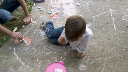 kalmak : Overhead of a young 4 - 5 year old boy helping an adult man color with chalk on a sidewalk Stok Video