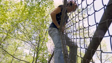 płot : Low angle of a man carefully climbing over a chainlink fence breaking into private property in slow motion Wideo