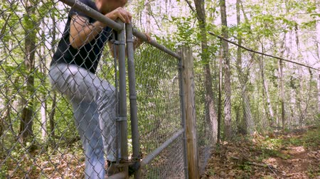 płot : Man in his 30s or 40s climbing over a chain link fence trespassing on private property