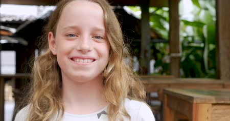 suçsuzluk : Portrait of a 10 - 11 year old happy caucasian girl smiling and looking at camera Stok Video