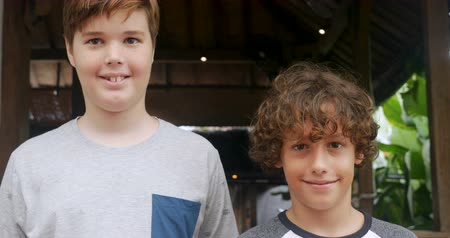 magasság : Portrait of a tall boy and short boy smiling and looking at the camera both at around 11 - 13 years of age