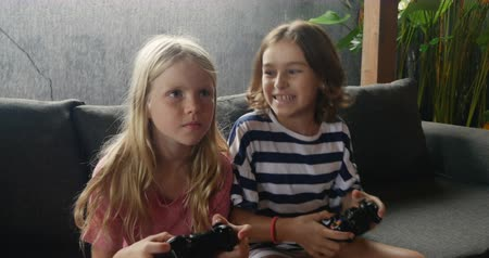 konkurenční : Two happy smiling young girls playing a video game together and talking while sitting on a sofa Dostupné videozáznamy