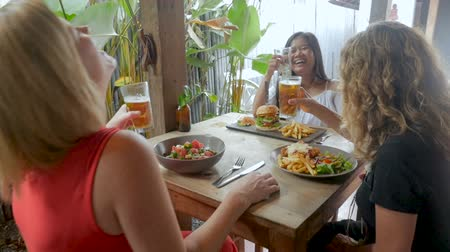 ebéd : Three women from different countries laughing and celebrating with drinks in slow motion - stabilized shot