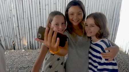 fotky : Three happy smiling diverse multi ethnic girl friends taking a selfie with a mobile phone in slow motion