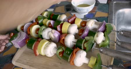 tomate cereja : Close up of a man or women brushing oil on healthy vegetable kebabs on metal skewers for the BBQ Stock Footage