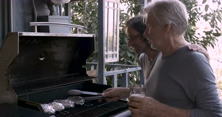 семидесятые годы : Happy man in his 40s puts his arm around an older senior adult man in his 70s while he is cooking potatoes wrapped in aluminum foil on a bbq grill