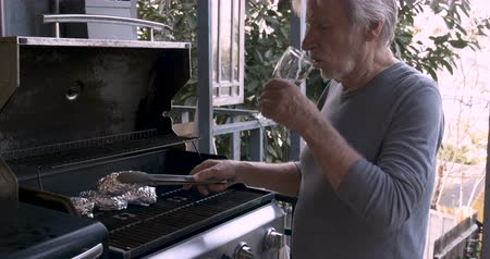 семидесятые годы : Healthy elderly senior man in his 70s drinking red wine turning potatoes wrapped in aluminum foil on a bbq grill