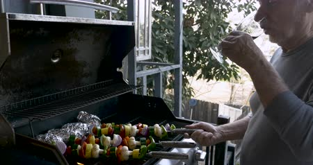 tomate cereja : Handsome healthy senior man in his 70s drinking red wine while barbecuing vegetable kebabs on a bbq grill Stock Footage