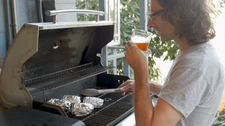 pişmiş : Handsome man with long hair drinking a craft beer turning baked potatoes on a bbq grill with metal tongs in slow motion