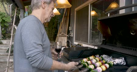 kebab : Happy attractive elderly senior man in his 70s drinking red wine and grilling vegetable kebabs on a bbq in his backyard