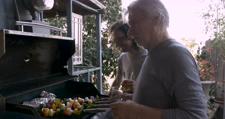 kebab : Older father and son grilling vegetable shish kebabs on a barbecue together while talking and spending time together