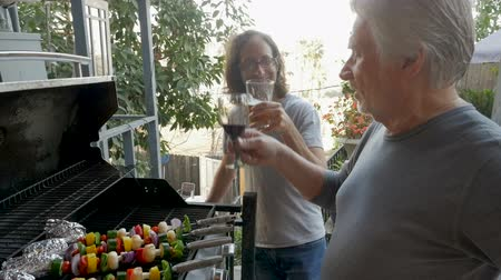 gyengéd : Older father and son grilling vegetable kebabs on a gas bbq grill cheering with beer and wine spending quality time together in slow motion