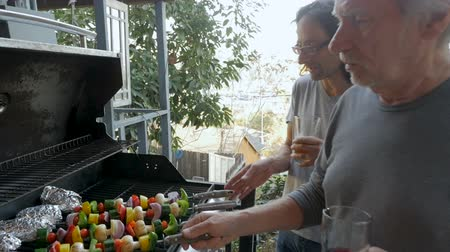 kebab : Two men, a man in his 40s and a senior man in his 70s cooking grilled vegetable kebabs and potatoes outside on a BBQ together in slow motion Stock Footage